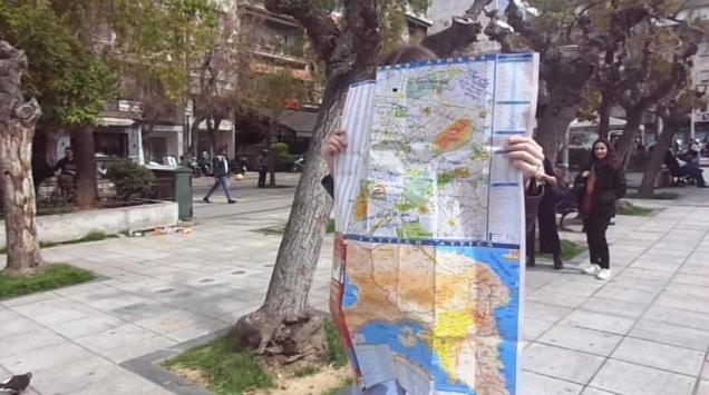Στιγμιότυπο από in situ performance στην οποία οι συμμετέχοντες περπατούσαν στην Πλατεία Βικτωρίας βλέποντας τον κόσμο μέσα από το κομμάτι του χάρτη που έχει αποσπαστεί